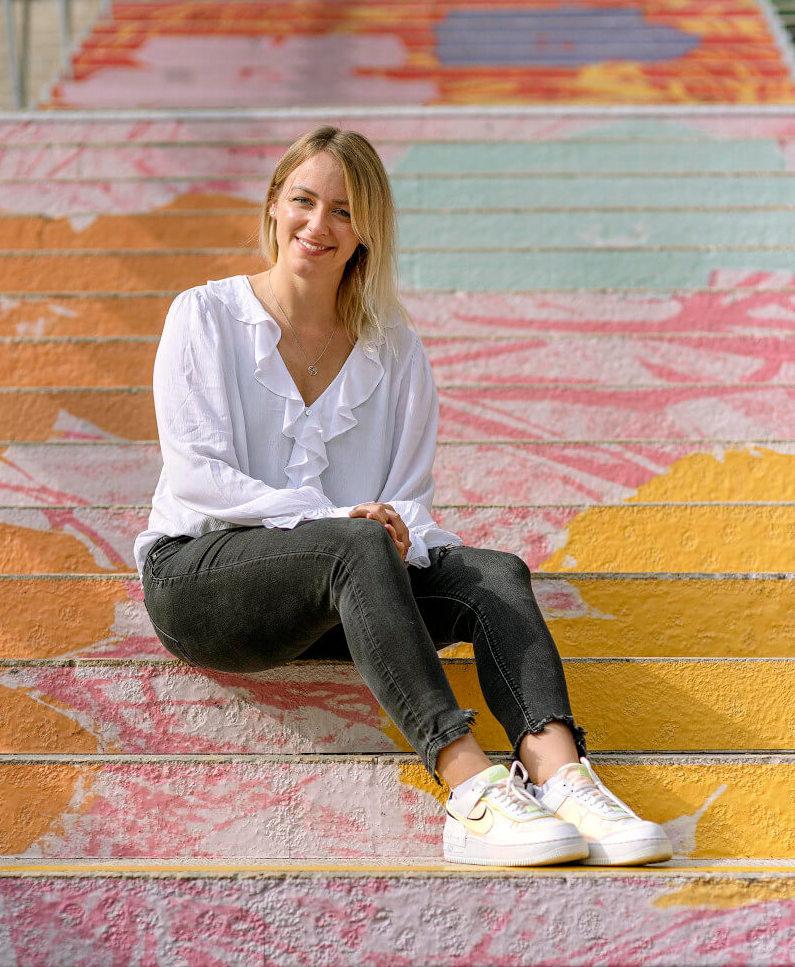Fotoaufnahme Jennifer Szeli sitzend auf bunten Stufe